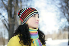 Woman in Snow. Beautiful brunetka winter on the street looks into the distance and laughs Stock Photo