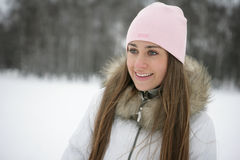 Woman in Snow. Beautiful girl winter on the street looks into the distance and laughs Stock Photo