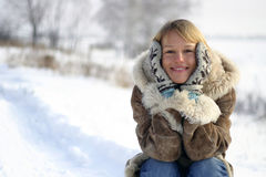 Woman in the Snow. Smiling woman sitting in the snow Royalty Free Stock Photo