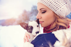 Woman in snow. Attractive young woman having fun outside in snow with her dog puppy Royalty Free Stock Photo