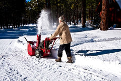 Woman snow blowing Stock Photo