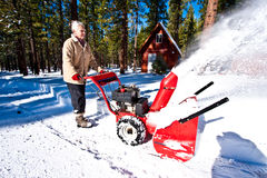 Woman snow blowing Royalty Free Stock Image