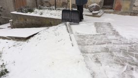 Woman with snow shovel clean the edge of the yard. In winter day stock video