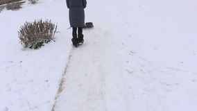 Woman with snow shovel pushing away snow. In winter day stock video footage