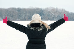 Woman in snow showing her back and facing forest with thumbs up Stock Photography