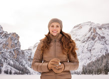 Woman with snowball outdoors among snow-capped mountains Stock Photos