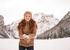 Woman with snowball outdoors among snow-capped mountains Stock Image