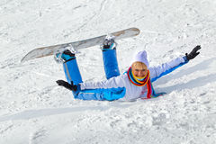 Woman with snowboard. Young laughing woman with snowboard lying in the snow Royalty Free Stock Photo