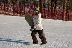 Woman with snowboard. Walking up snow-covered slope royalty free stock photography