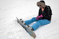 Woman with snowboard rests on snow Royalty Free Stock Photo