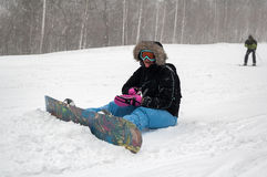 Woman with snowboard rests on snow Stock Images