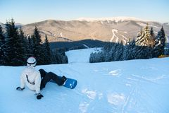 Woman with snowboard sits on fresh snow top of mountain Royalty Free Stock Image