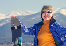 Woman with snowboard on the snow hill Stock Image