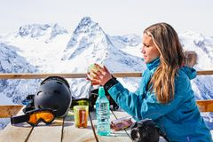Woman snowboarder drinking warm tea in the rustic wooden outdoor cafe mountain summit. Lifestyle adventure concept. Alpine view. With snow covered peaks. Active royalty free stock images