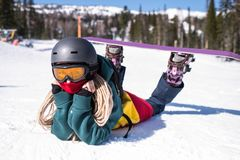 Woman snowboarder lying on a snowy slope. Relax. stock image
