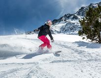 Woman snowboarder in motion in mountains Stock Photos