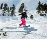 Woman snowboarder in motion in mountains Stock Photography
