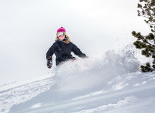 Woman snowboarder in motion in mountains Stock Images