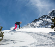 Woman snowboarder in motion in mountains Stock Image