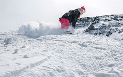 Woman snowboarder in motion in mountains. Young woman snowboarder in motion on snowboard in mountains Royalty Free Stock Photography