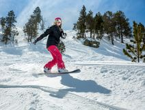 Woman snowboarder in motion in mountains. Young woman snowboarder in motion on snowboard in mountains Stock Images