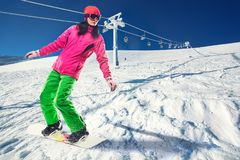 Woman snowboarder skiing in the mountains Stock Photos