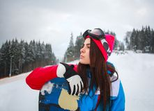 Woman snowboarder in winter at ski resort on background of pine Royalty Free Stock Photos