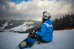 Woman snowboarder in winter at ski resort sits Royalty Free Stock Photo