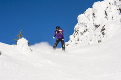 Woman Snowboarding in Alpine Terrain Stock Photography