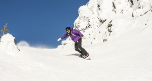 Woman Snowboarding in Alpine Terrain Stock Images