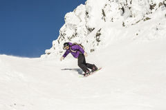Woman Snowboarding in Alpine Terrain Stock Image