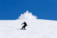 Woman snowboarding on slopes of Pradollano ski resort in Spain