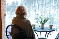 Woman with snowdrops and drink mugs on balcony, Winter time. Woman with snowdrops and drink mugs on balcony stock photos