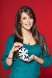 Woman with snowflake. Against red background Stock Image
