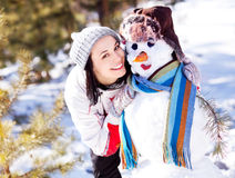 Woman with a snowman Stock Photos