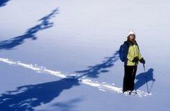 Woman Snowshoeing. A woman snowshoeing across a winter landscape stock photos