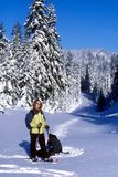 Woman Snowshoeing. A woman snowshoeing across a winter mountain landscape royalty free stock images