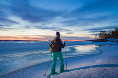 Woman snowshoeing by the lakeside Royalty Free Stock Image