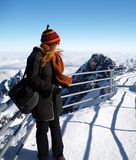 Woman on snowy mountain. Attractive young woman in woollen hat stood on path at summit of wintry mountain stock image