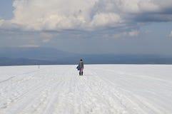 Woman on snowy mountain plateau Stock Photo