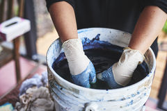 A woman soaking fabric in indigo dye. A woman with her hands in a bucket of indigo dye royalty free stock image