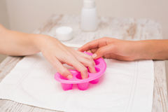 Woman soaking her nails in nail bowls Royalty Free Stock Photos