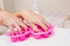 Woman soaking her nails in nail bowls Stock Photo