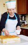 Woman soaks juice cake Stock Image