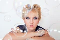 Woman between soap bubbles Stock Photo