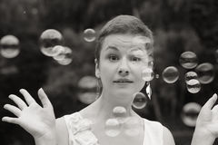 Woman with soap bubbles. Outdoor duotone emotional humorous portrait of young attractive young woman with soap bubbles, selective focus Stock Image