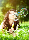 Woman and soap bubbles in park. Beautiful young girl lying on th Stock Photos