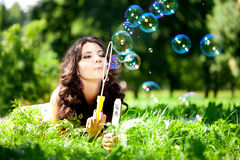 Woman and soap bubbles in park. Beautiful young girl lying on th Stock Image