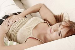 Woman on a sofa. Red-haired young girl, woman on a sofa Royalty Free Stock Images