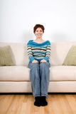 Woman on sofa. Woman in casual clothing sitting on a sofa Royalty Free Stock Images
